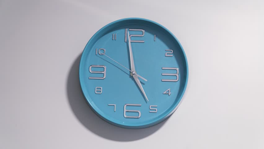 Timelapse of a blue clock on a white wall. The clock starts ticking at 5 and ends at 12.