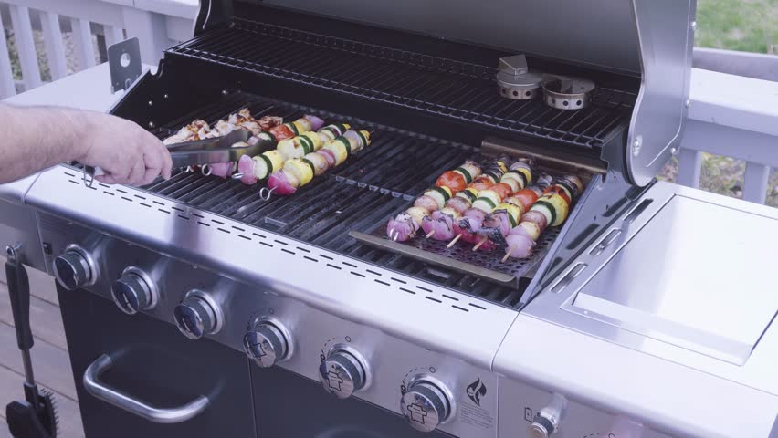 Step by step. Grilling veggie skewers and chicken kebabs on outdoor gas grill.