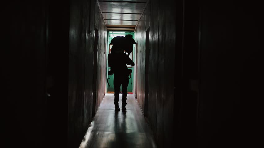 Silhouette of a tourist dancing in the hallway of the hotel. Happy traveler with a large backpack moving his hands in the dark. Slow-motion. | Shutterstock HD Video #1010902727