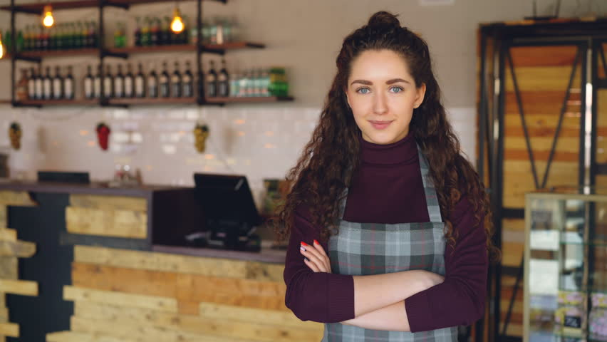 Portrait of attractive confident woman small business owner standing in her opening coffee shop and smiling looking at camera. Coffee house interior in background.