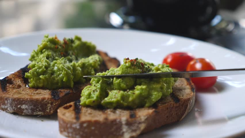 Spreading Mashed Avocado On Toast. Healthy Vegan Breakfast. #1010912597
