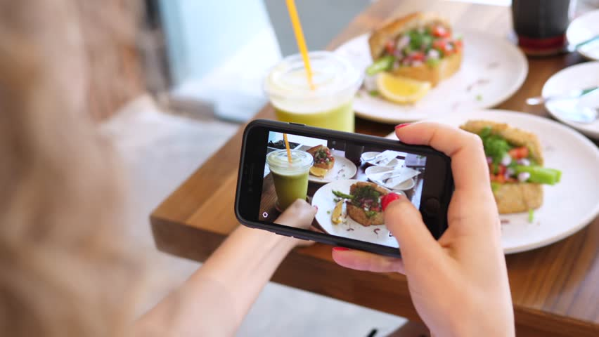 Woman Food Blogger Taking Photos Of Vegan Healthy Food By Cellphone In Cafe #1010916269