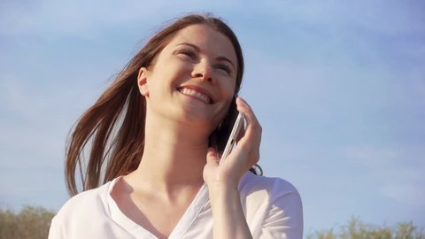 Happy smiling young woman in white shirt using mobile against blue sky. Smiling female talking with friends via cellphone in slow motion