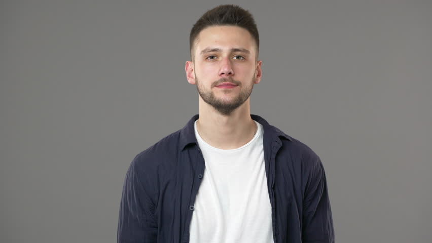 Portrait of perplexed man in casual clothing shrugging and expressing misunderstanding with throwing up hands, isolated over gray background. Concept of emotions Royalty-Free Stock Footage #1010927732