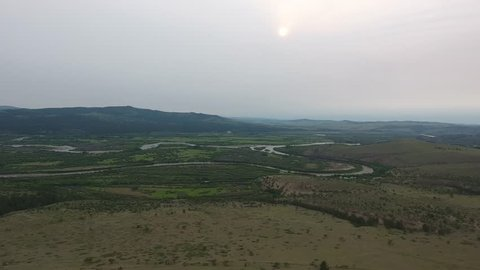 Aerial drone shot going up over a large river on Mongolian/Russian border. Sunset, cloudy weather, medium altitude flight.
