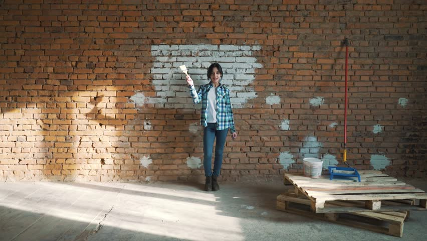 Girl Builder on brick wall background dancing and paints the wall with white paint | Shutterstock HD Video #1010937182