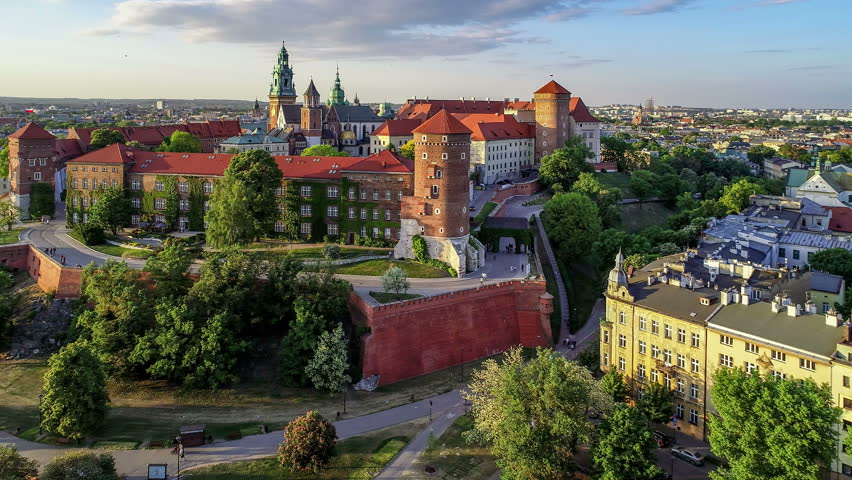 Krakow, Poland. Wawel royal Castle and Cathedral, Vistula River, park, promenade and walking people. Cracow old city with historic churches in the background. Aerial 4K flyby video at sunset in spring Royalty-Free Stock Footage #1010938622