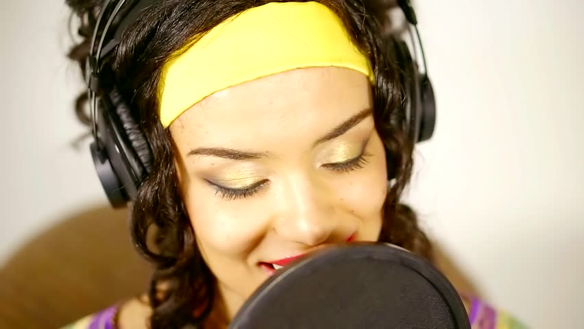 african woman is singing in a large professional microphone in a record studio, close-up