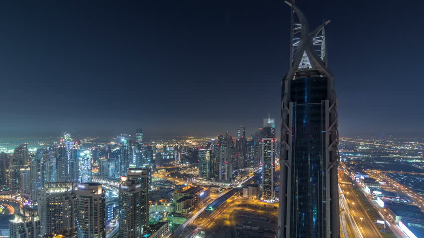 Dubai Downtown skyscrapers night timelapse modern towers panoramic view from the top in Dubai, United Arab Emirates. Traffic on the Sheikh Zayed road near business bay