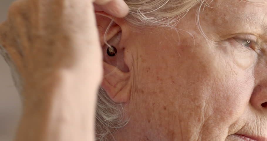 An attractive elderly woman in her 70s adjusts her hearing aid and puts it in her ear