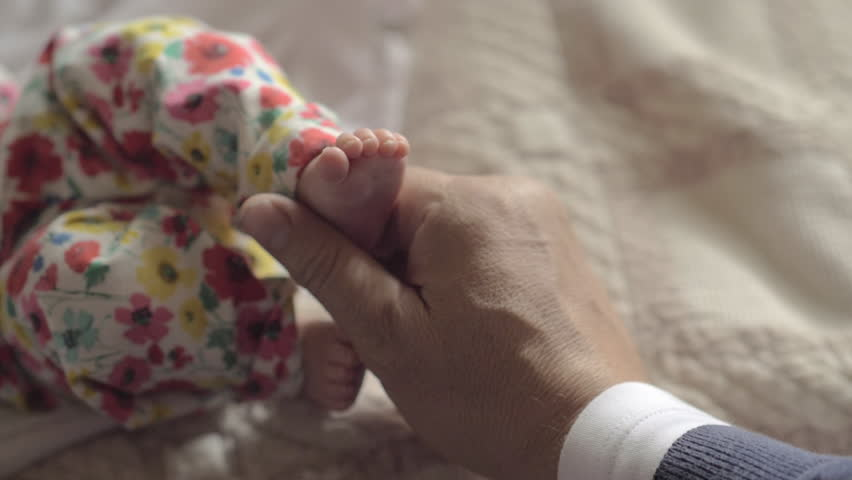 Slow motion close-up shot of grandfather touching little feet of baby granddaughter