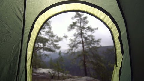 Wanderlust view from a tent in rainy weather outdoors in the wild coniferous forest near a cliff