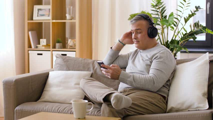 happy man with smartphone and headphones listening to music at home #1010982032