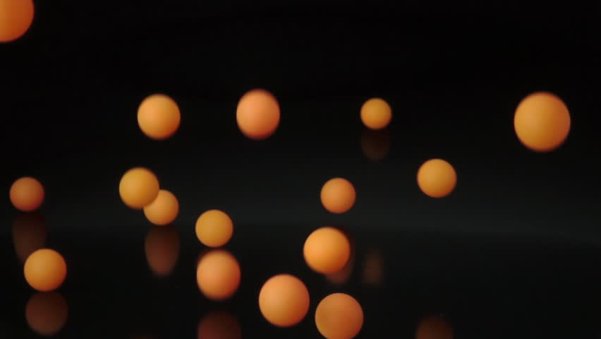 many orange balls falling and bouncing on black surface slow motion