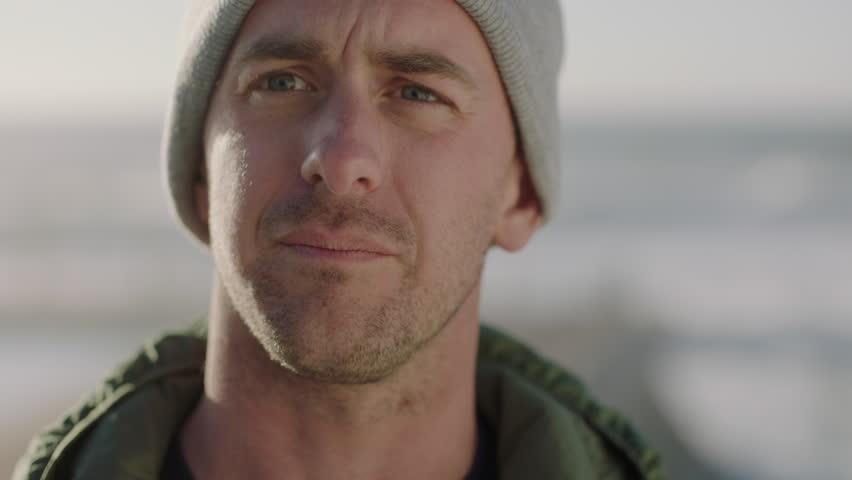 close up portrait of attractive young man looking serious worried caucasian male wearing beanie hat concerned pensive #1010987204