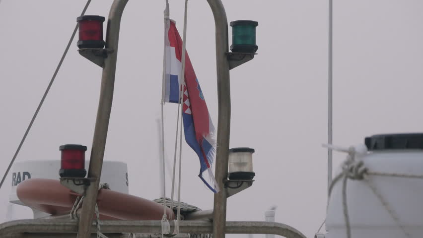 Novigrad, Croatia - April, 2016: Croatian flag hanging in the seaport of Novigrad on a foggy day | Shutterstock HD Video #1010987534