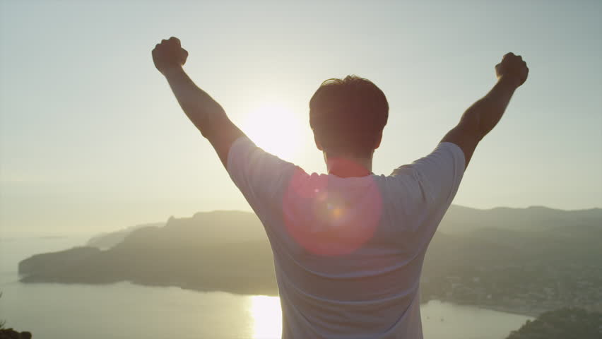 SLOW MOTION CLOSE UP: Cheerful young man raising his hands high on top of the big mountain above the ocean at beautiful golden sunset #1011005321