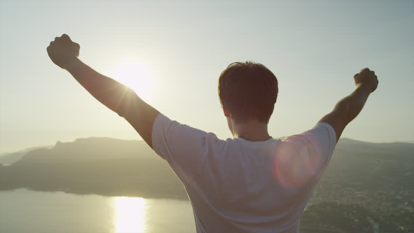 SLOW MOTION CLOSE UP: Successful young man with arms raised high standing on top of the ocean cliff above the city at beautiful golden sunset, sun shining through the hands #1011005324