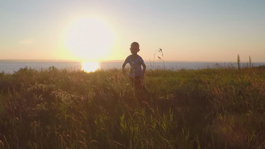 The child run in the field at sunset. Slowmotion  | Shutterstock HD Video #1011015143