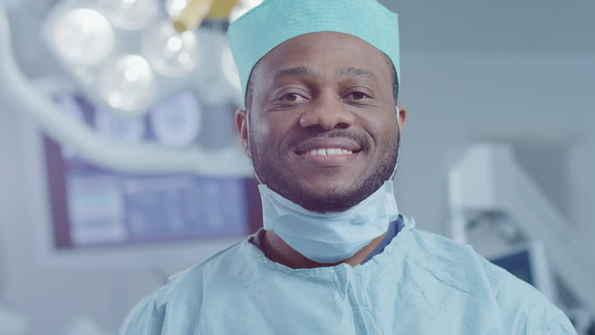 Portrait of the Professional Surgeon Takes off Surgical Mask after Successful Operation. In the Background Modern Hospital Operating Room. Shot on RED EPIC-W 8K Helium Cinema Camera.