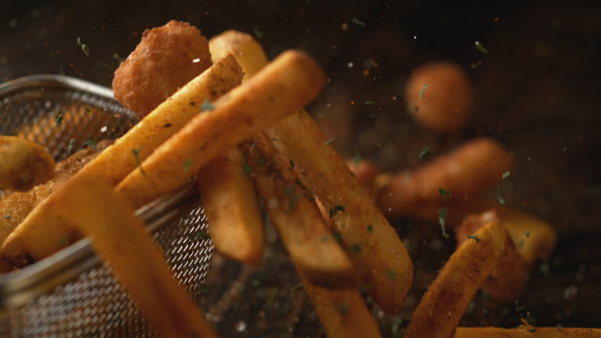 Camera follows french fries falling on wooden table. Shot with high speed camera, phantom flex 4K. Slow Motion.   Shutterstock HD Video #1011040607