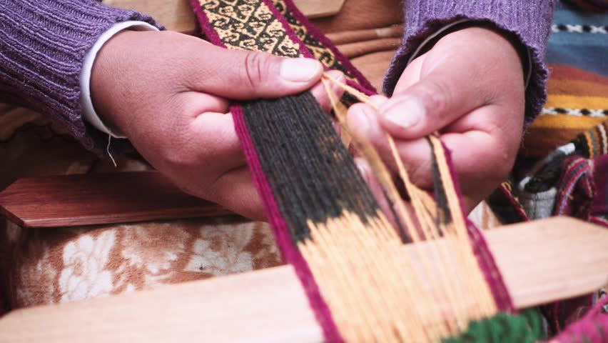 Indigenous woman selects the yarn meanwhile weaves yarn a foot loom at downtown Cusco, Peru.