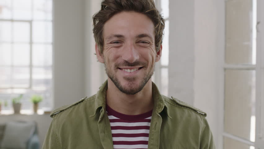 Slow motion portrait of young attractive man enjoying successful lifestyle smiling cheerful looking at camera close up | Shutterstock HD Video #1011074708