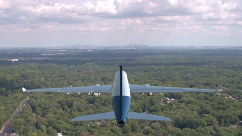 AERIAL, CLOSE UP: Large freight plane flying over a vast green forest covering the urban outskirts of New York. Flying behind a commercial airplane preparing for landing at approaching Newark airport.