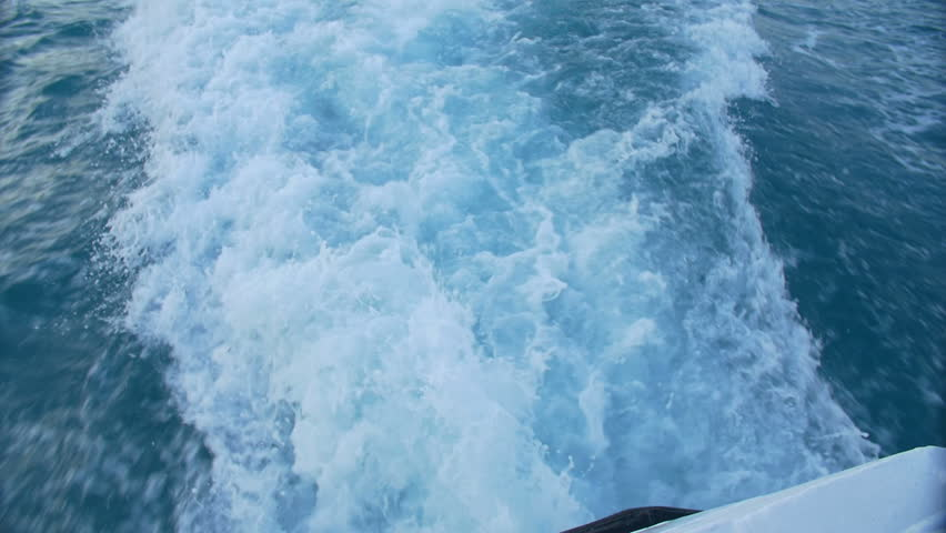 The wake of a boat as seen from the side of a ship.   Shutterstock HD Video #1011084647