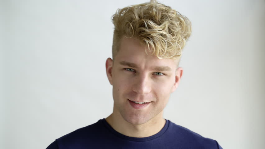 Young man with blonde hair turning head, studio shot. #1011085796