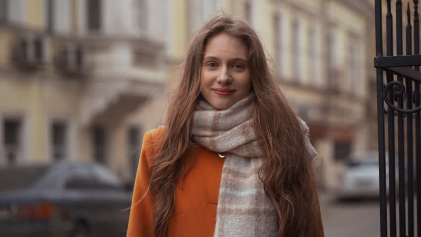 Portrait of positive european woman 20s wearing coat and scarf smiling and showing ok sign, while walking on city street during autumn windy day
