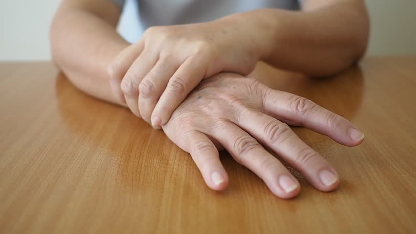 Parkinson's disease symptoms. Close up of tremor (shaking) hands of Middle-aged women on wooden table. Mental health and neurological disorders.