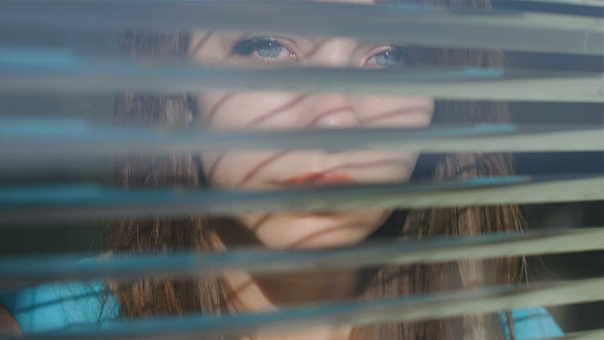 COVID 19 Isolation Concept. Stay at home quarantine. Beautiful young woman looking out the window through the blinds to the street.