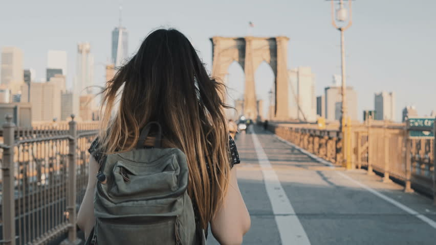 Camera follows young woman with backpack walking along Brooklyn Bridge, New York on a beautiful sunny summer day 4K. | Shutterstock HD Video #1011108743