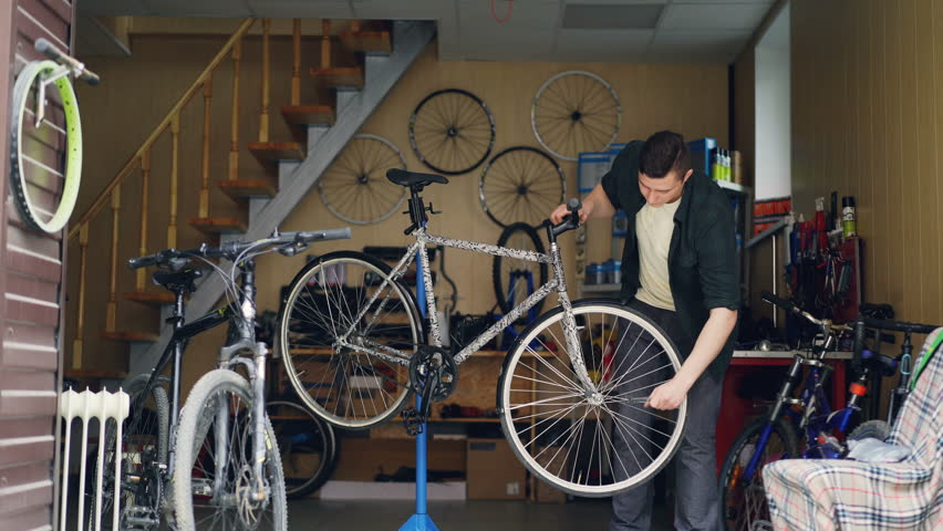 Skilled male mechanic is fixing broken bicycle wheel with wrench then turning it and checking. Many cycles, spare parts, tools and equipment are visible. | Shutterstock HD Video #1011118052