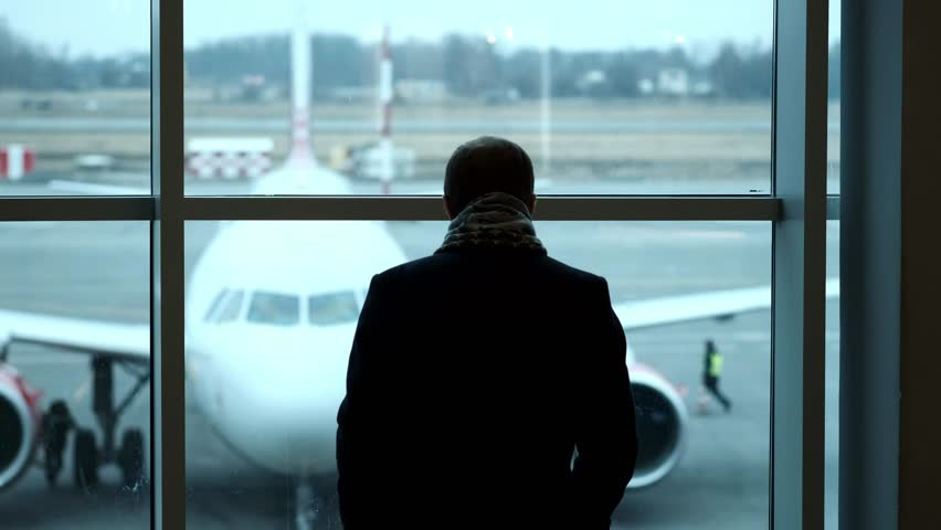 Old Man stand at full height, gaze out airport terminal window, silhouette view. Looks at the plane at the airport | Shutterstock HD Video #1011120122