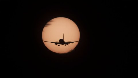 Silhouette of jumbo jet plane landing with big sun in the background, high contrast 4k version
