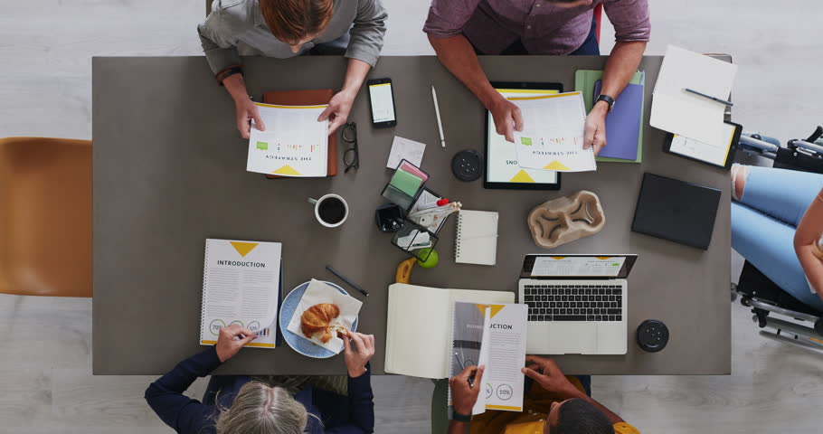 top view of multi ethnic business team brainstorming innovative ideas for startup company developing market strategy time lapse close up #1011129944