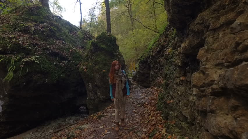 A red-haired young woman tourist with a backpack travels through the wild among rivers, waterfalls and mountains | Shutterstock HD Video #1011133892
