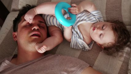Young tired father sleep near a little child in a bed