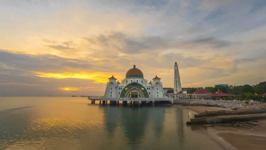Dramatic Time lapse of sunset and scattered clouds at a mosque in Melaka, Malaysia. 4K resolution, 3840 x 2160. Day to Night.