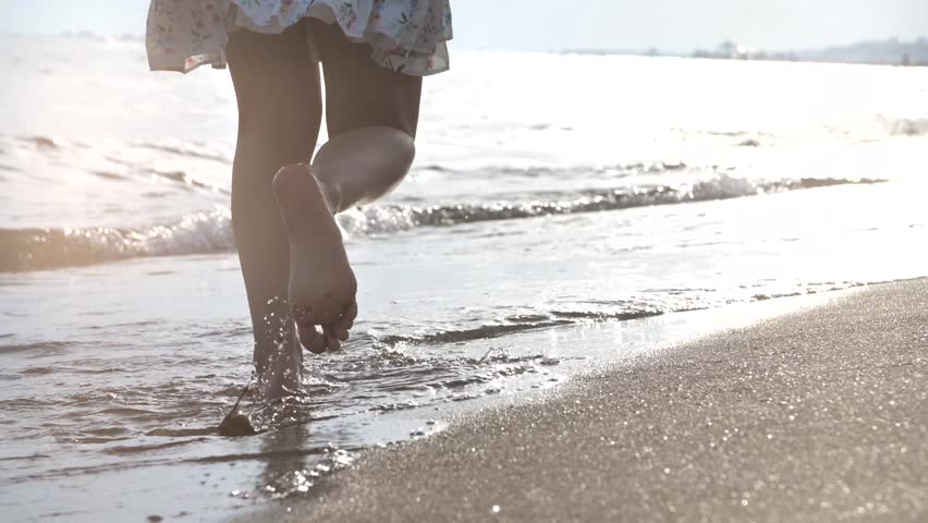 Girl running on the waves at sunset on sandy beach. Concept of happiness. | Shutterstock HD Video #1011149249