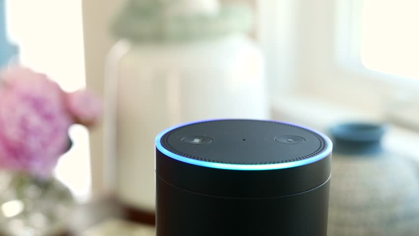 Amazon Alexa / Amazon Echo is on a table near Window.  Activates. For editorial use.