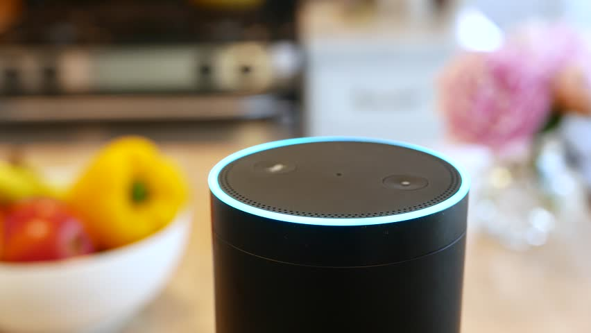Amazon Alexa closeup in a kitchen.  Pretty flowers and fruit in Background.  Smart speaker activates in a kitchen environment. For editorial use.