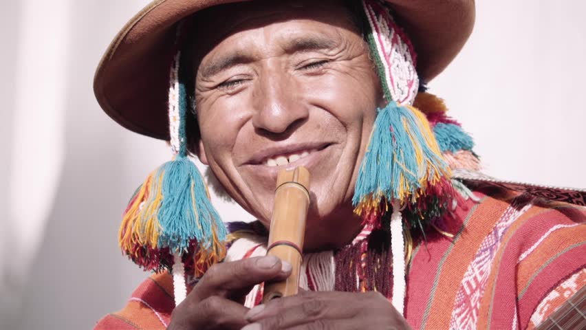 Native quechua man using a colorful handcrafted chullo and a highlander hat, singing with his guitar on the alleys of Cusco Royalty-Free Stock Footage #1011161774