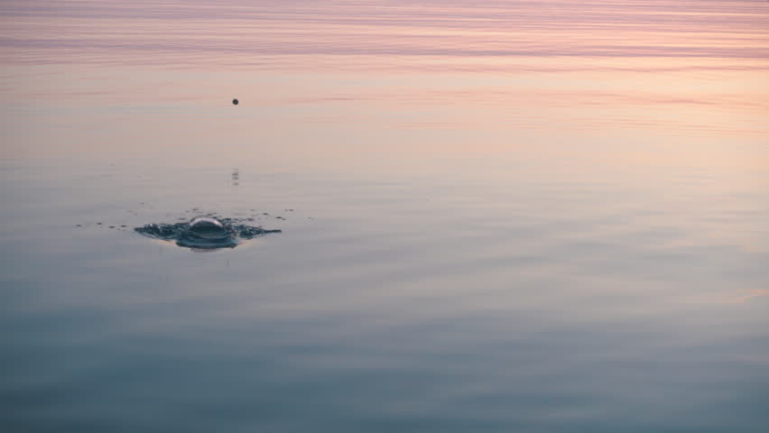 Stone skipping on beautiful calm water, majestic sunrise around, 4k video.