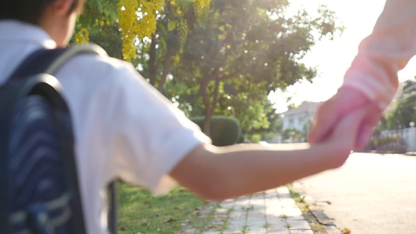 Asian mother holding hand of little son with backpack outdoors, back to school    Shutterstock HD Video #1011169532