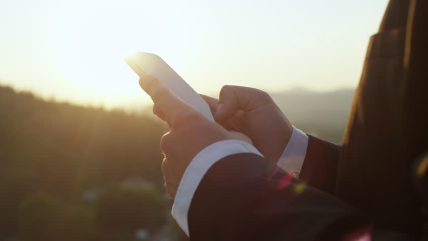 SLOW MOTION, CLOSE UP, DOF: Detail of hands of a man in black and white suit writing messages and business correspondence on modern telephone. Unrecognizable person working on cellphone at sunrise #1011186572