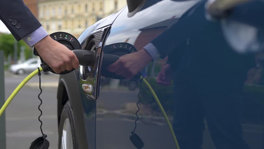 Slow-mo Reveal of Electric Socket Charging New, Efficient Car in Street
