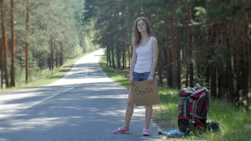 Young beautiful woman hitchhiking standing on the road with a backpack on a table with an inscription SOUTH 4k | Shutterstock HD Video #1011208532